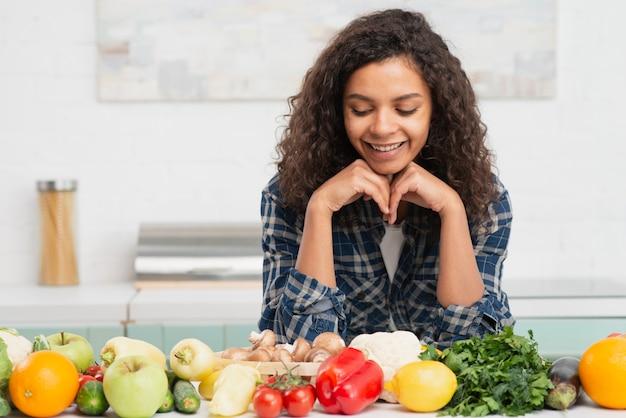 Portret van glimlachende vrouw die op groenten kijkt