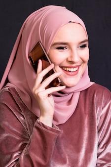 Portret van glimlachende vrouw die op mobiele telefoon spreekt