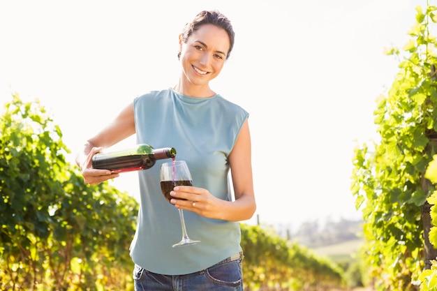 Portret van glimlachende vrouw die rode wijn van fles in glas gieten