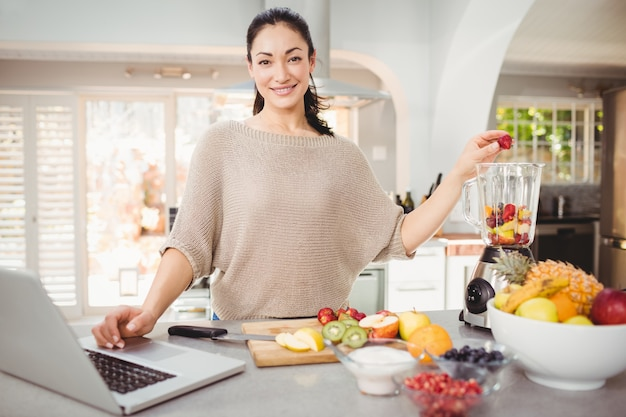 Portret van glimlachende vrouw die vruchtensap voorbereiden terwijl het werken aan laptop