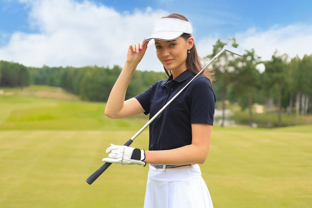 Portret van glimlachende vrouw die zich met golfclub in golfbaan bevindt