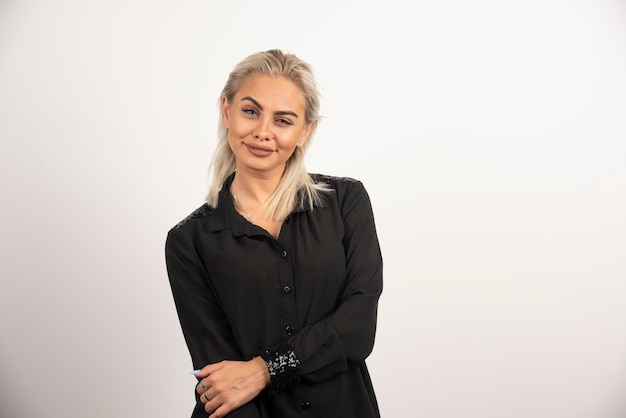 Portret van glimlachende vrouw in het zwarte overhemd stellen op witte achtergrond. hoge kwaliteit foto