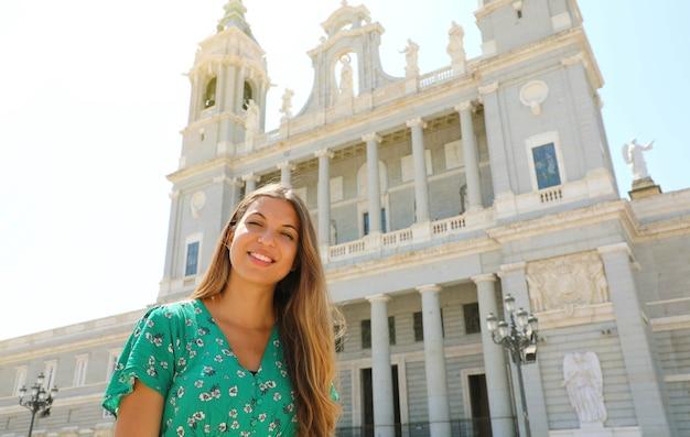 Portret van glimlachende vrouw in madrid met almudena kathedraal, spanje