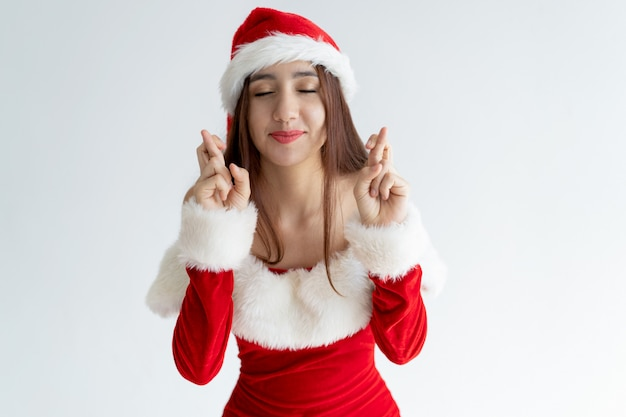Portret van glimlachende vrouw in santa claus-kleding die wens maken