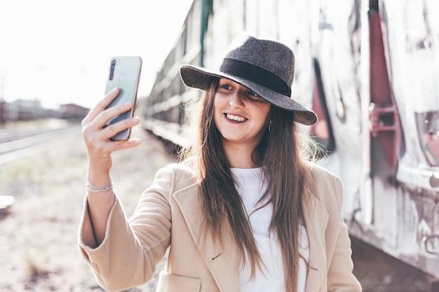 Portret van glimlachende vrouw met hoed en beige jas die haar telefoon op een verlaten treinstation met behulp van.