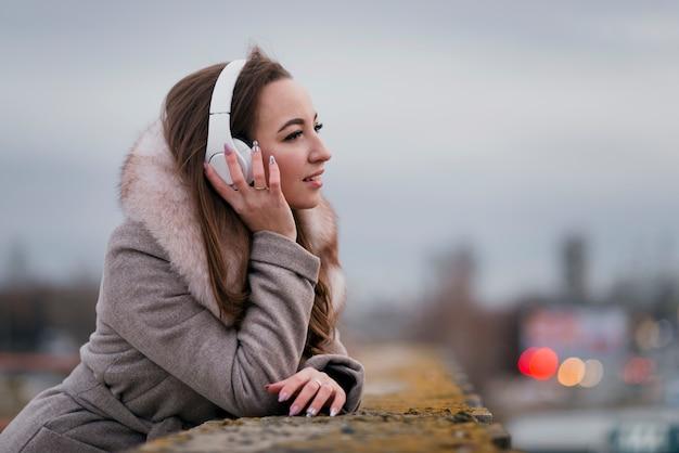 Portret van glimlachende vrouw met hoofdtelefoons op dak