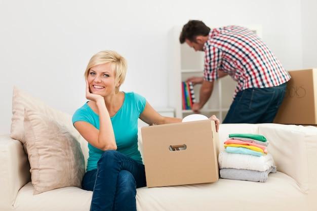 Portret van glimlachende vrouw tijdens het verfraaien van nieuwe woonkamer