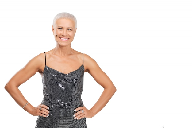 Portret van glimlachende vrouw van middelbare leeftijd in cocktailkleding met handen op de taille