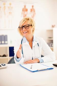 Portret van glimlachende vrouwelijke arts die een handdruk aanbiedt