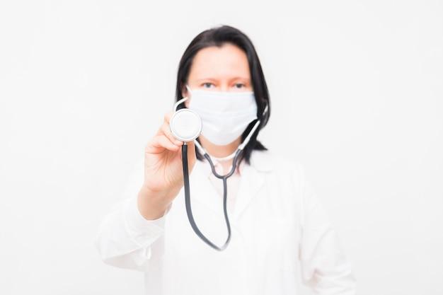 Portret van glimlachende vrouwelijke arts in masker op witte ruimte