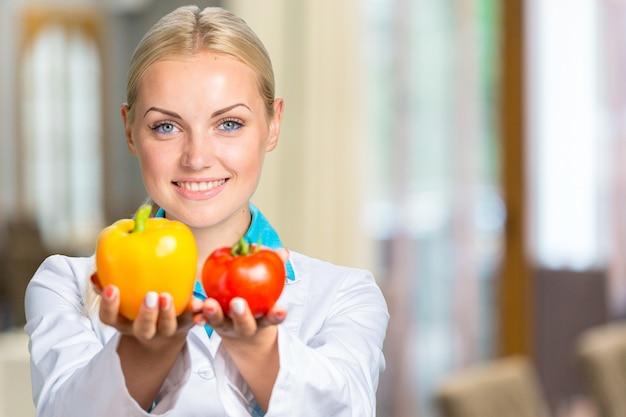 Portret van glimlachende vrouwelijke arts in witte toga die verse groenten geïsoleerd houden