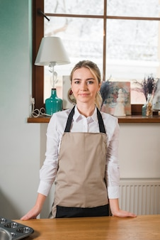 Portret van glimlachende vrouwelijke bakker die zich achter de houten lijst bevindt