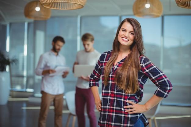 Portret van glimlachende vrouwelijke directeur die zich met handen op heup bevindt