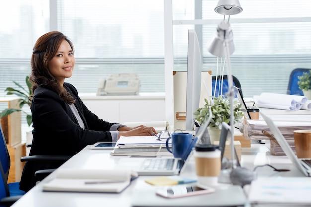Portret van glimlachende vrouwelijke ondernemer die op computer werkt en e-mails beantwoordt van klanten en zaken...