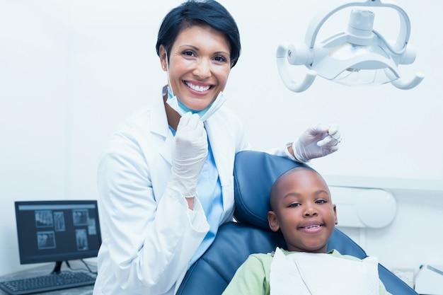 Portret van glimlachende vrouwelijke tandarts die jongenstanden onderzoeken
