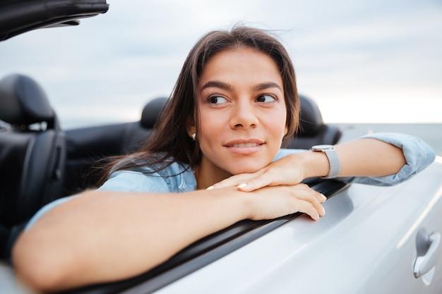 Portret van glimlachende vrouwenzitting in haar converteerbare auto op strand