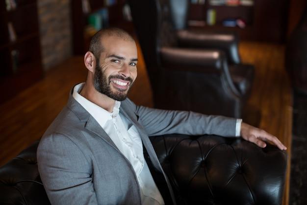 Portret van glimlachende zakenman zittend op de bank in wachtruimte