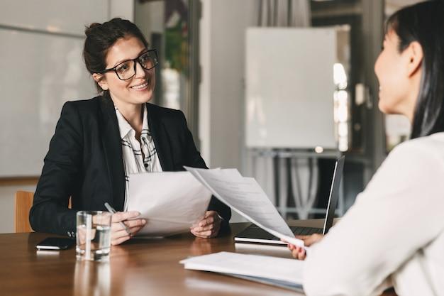 Portret van glimlachende zakenvrouw met cv en praten met vrouwelijke kandidaat, tijdens zakelijke bijeenkomst of sollicitatiegesprek - bedrijfs-, carrière- en plaatsingsconcept
