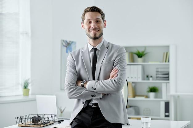 Portret van glimlachende zelfverzekerde jonge zakenman in zwarte stropdas die zich met gekruiste wapens dichtbij bureau in bureau bevindt