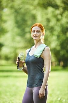 Portret van glimlachende zelfverzekerde roodharige rijpe vrouw met handdoek op de fles water van de schouderholding in de zomerpark