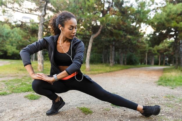 Portret van goedgebouwde afrikaanse amerikaanse vrouwen20s die zwart trainingspak dragen die oefeningen doen, en haar benen in groen park strekken