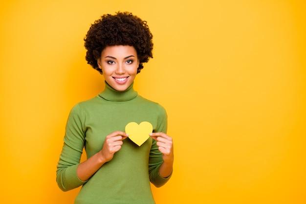Portret van golvende vrolijke leuke aardige mooie vrouw die zich dichtbij lege ruimte bevindt die geel hart van liefde houdt.