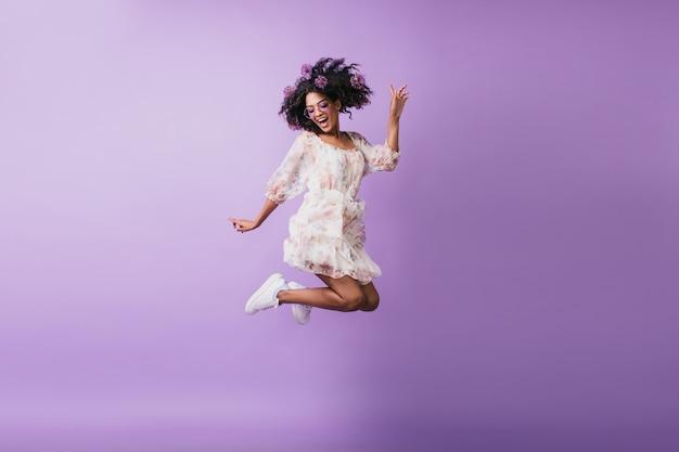 Portret van grappig afrikaans meisje in het witte kledij het springen. blithesome brunette jonge vrouw positieve emoties uitdrukken.