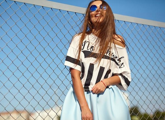 Portret van grappig gek glamour modieus het glimlachen mooi jong vrouwenmodel in de heldere vrijetijdskleding die van de hipsterzomer in de straat achter ijzergrating en blauwe hemel stellen