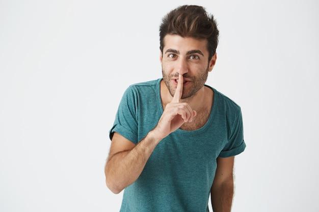 Portret van grappig knap kaukasisch mannetje in blauw t-shirt. met goed haar en baard, lach terwijl je het geheim aan zijn vriend vertelt en vraag het aan niemand te vertellen.