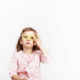 Portret van grappig meisje die gele stuk speelgoed plastic met de hand gemaakte glazen tegen wit maken