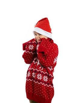 Portret van grappig meisje in rode kerstmuts en rode gebreide oversized kersttrui met ren...