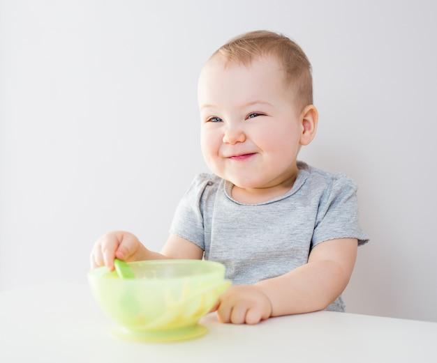 Portret van grappig schattig babymeisje dat in de keuken eet
