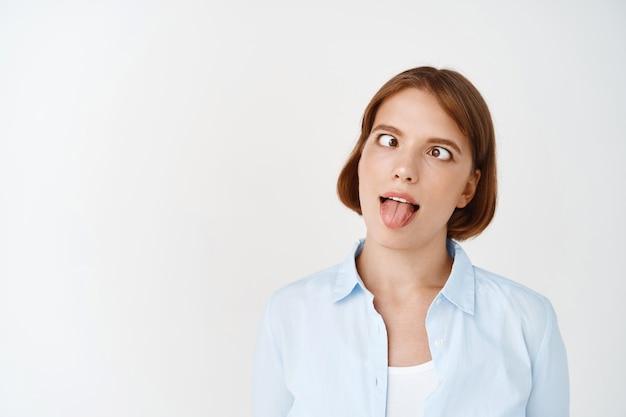 Portret van grappig speels meisje met loensende ogen en tong dom tonen, gezichten maken, blauwe kantoorblouse dragen, gekke emotie hebben, tegen de witte muur staan