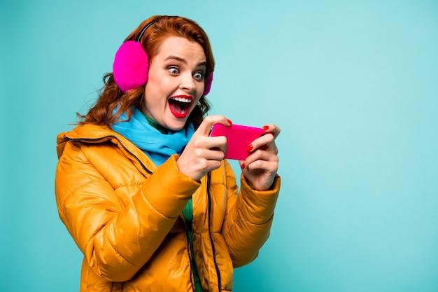 Portret van grappig verbaasd dame houden telefoon verslaafd videogames speler open mond opgewonden dragen trendy casual oorhoezen gele overjas sjaal.