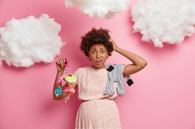 Portret van grappige aanstaande vrouw met zwangere buik, poseert met kleding en speelgoed voor baby, draagt jurk, heeft geen ervaring met het moederschap, voelt hoe kind buik met been duwt. moederschap concept
