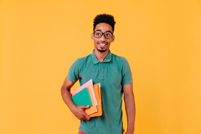 Portret van grappige afrikaanse student in groen t-shirt. foto van zalige zwarte jongen die in glazen boeken en handboeken houdt na examens.