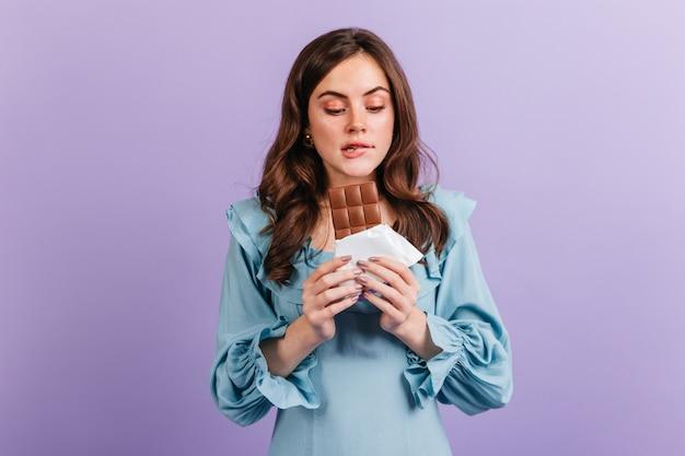 Portret van grappige brunette vrouw haar lip bijten in afwachting van smakelijke lunch. meisje in blauwe jurk kijkt naar heerlijke chocolade.
