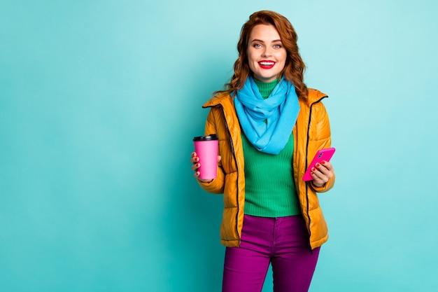 Portret van grappige dame houden warme koffiemok drank browsen telefoon lopen straatkleding casual gele overjas sjaal broek pullover.