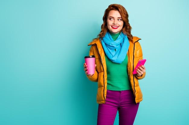 Portret van grappige dame houden warme koffiemok drank slimme telefoon telefoon lopen straatkleding casual gele overjas sjaal broek groene trui.