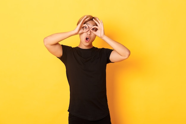 Portret van grappige en schattige aziatische blonde kerel die vingers glazen en grimassen, staande gele muur maakt