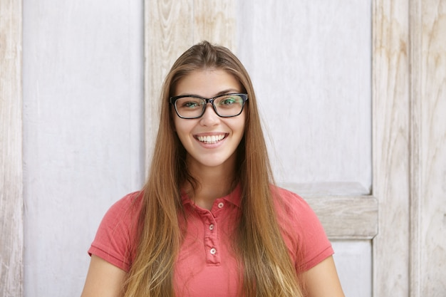 Portret van grappige en vrolijke jonge blanke vrouw, gekleed in rechthoekige bril en poloshirt op zoek gelukkig lachend met haar witte tanden