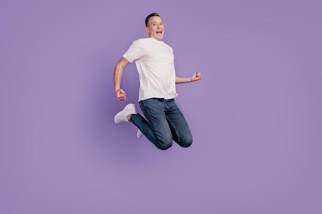 Portret van grappige energieke kerel sprong verheugen op paarse achtergrond