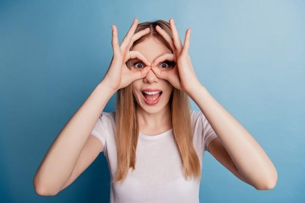 Portret van grappige funky dwaze dame vingers maken verrekijker gebaar dragen wit t-shirt geïsoleerd op blauwe kleur achtergrond