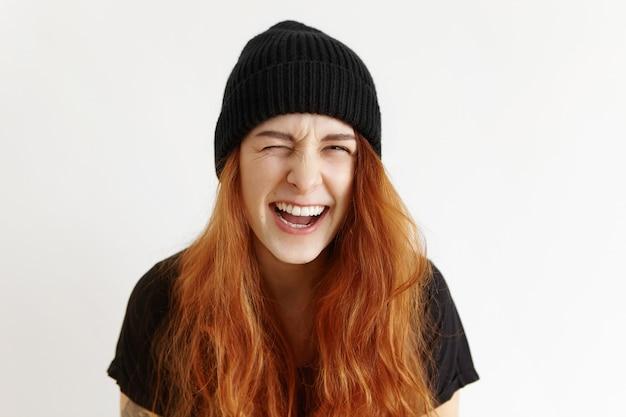 Portret van grappige funky tienermeisje met slordig haar stijlvolle hoed en t-shirt dragen