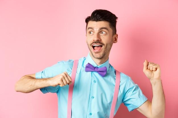 Portret van grappige jonge kerel schiet op en rennen, opzij kijken met opgewonden gezicht, haasten om promo-aanbieding te krijgen, staande over roze achtergrond.
