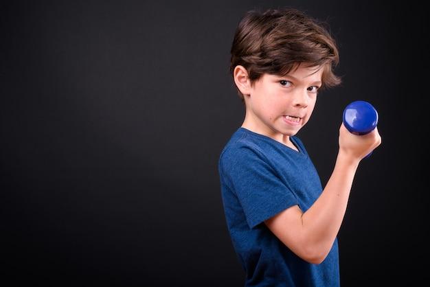 Portret van grappige jonge knappe jongen trainen met halters
