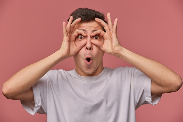 Portret van grappige jonge man met kort kapsel gek en grimassen over roze achtergrond, hand in hand rond de ogen en gezichten trekken, vrijetijdskleding dragen