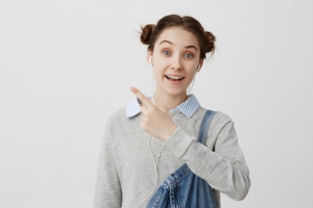 Portret van grappige jonge vrouw, gekleed in denim wijzende wijsvinger weg. gelukkig gezichtsuitdrukkingen van vrouwelijke modeontwerper ontspannen voor presentatie met rustige muziek. kopieer ruimte