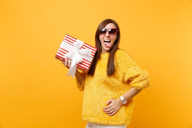 Portret van grappige jonge vrouw in rode bril die tong toont, rode doos met cadeau vasthoudt, aanwezig geïsoleerd op felgele achtergrond. mensen oprechte emoties, lifestyle concept. reclame gebied.