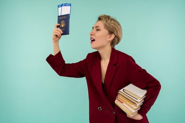 Portret van grappige jonge vrouw met paspoort en instapkaart en boeken laat voor vlucht op blauwe achtergrond. grenzen openen. begin van vliegreizen na een pandemie.